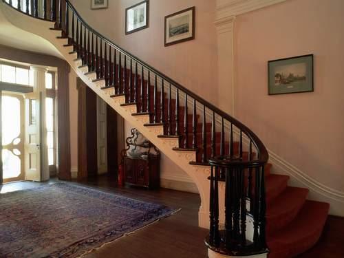 Деревянные перила лестницы в интерьере дома